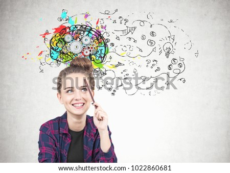 Smiling teen girl in a checkered shirt is sitting with a pencil near her forehead and thinking. She is looking at a colorful brain sketch with cogs on it and a business idea sketch.
