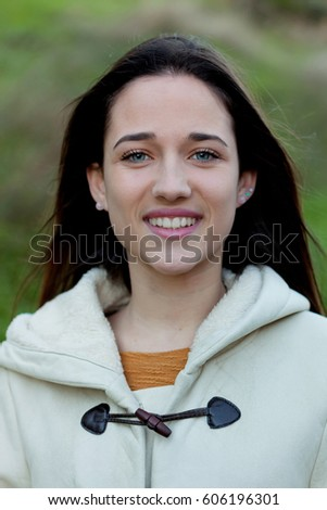 Stock Photo Smiling teen girl outside with a natural green of background