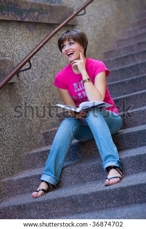 smiling teen girl with book on the stairs