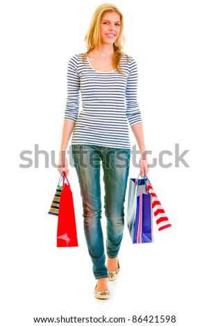 Smiling teen girl with shopping bags making step isolated on white