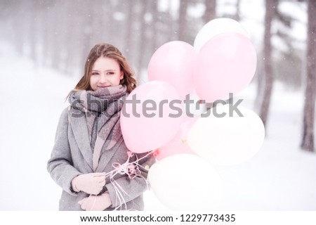 Smiling teen girl 16-18 year old holding balloons outdoors over snow background. Looking at camera. Winter season.