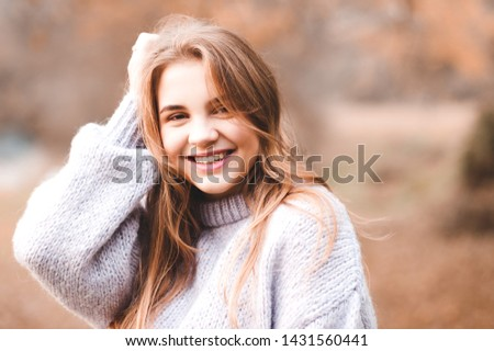 Smiling teen 14-16 year old wearing warm sweater outdoors. Looking at camera. Autumn season. 20s.