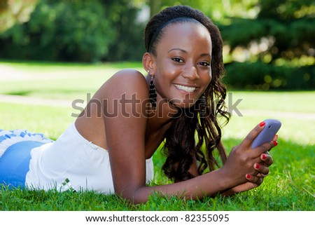 Smiling teenage black girl using a phone, lying on the grass
