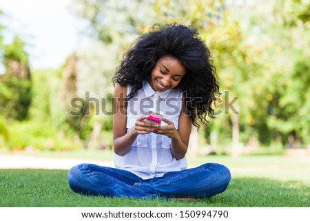 Smiling teenage black girl using a phone, sitting on the grass - African people