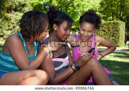Smiling teenage black girls using a mobile phone at park