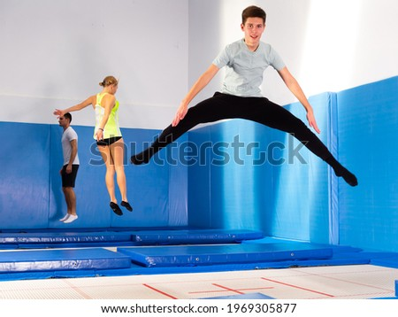 Smiling teenage boy jumping on trampoline in sports center. Youth sport lifestyle concept Stock fotó ©