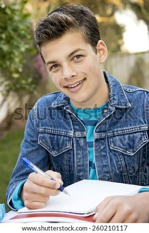 Smiling teenage boy studying outside with notebooks and pen, sitting, denim jacket