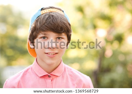 Smiling teenage boy 13-14 year old wearing cap and pink shirt posing in park close up. Looking at camera. Spring season.
