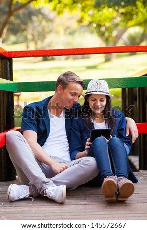 smiling teenage couple using tablet computer sitting outdoors