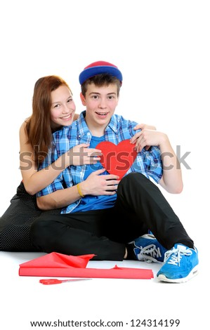 Smiling teenage girl and boy holding a valentine cut out from red paper with scissors over white background