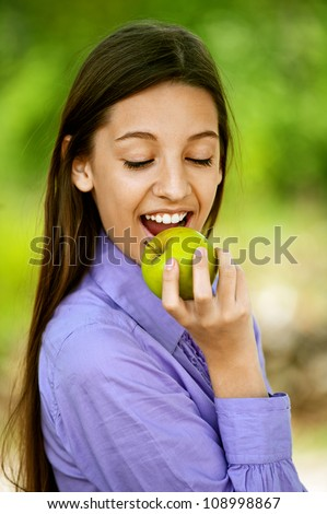 Smiling teenage girl biting an apple, against green of summer park.