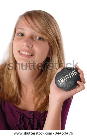 Smiling teenage girl holding a rock with the word Imagine in white letters printed on it.