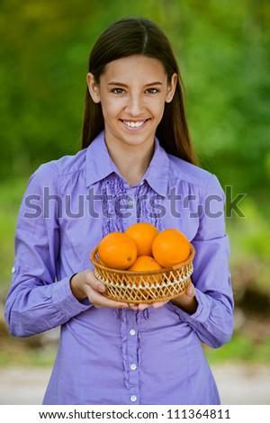 Smiling teenage girl holding basket of oranges, against green of summer park.