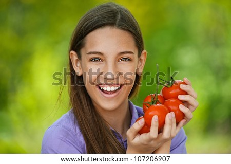 Smiling teenage girl holding red tomatoes, against green of summer park.