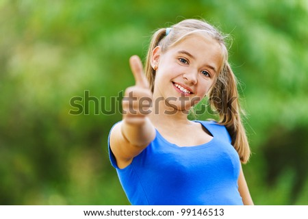 Smiling teenage girl in blue dress shows hand sign that she is doing fine, against background of green summer park.