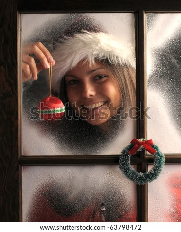 Smiling Teenage girl in window covered with frost holding a Christmas Ornament in front of her face vertical composition