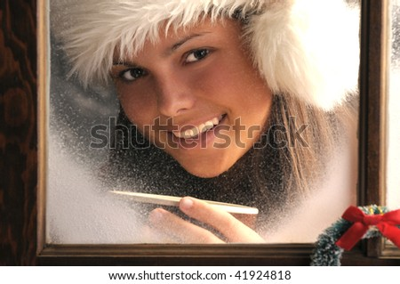 Smiling Teenage girl in window with frost holding a mug of Hot Cocoa Horizontal composition close up