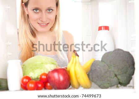 Smiling teenage girl looking inside of a refrigerator with fresh fruits and vegetables.