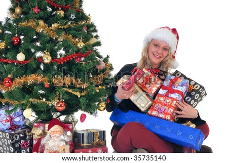 Smiling teenage girl next to Xmas, Christmas three with hands full of presents, gifts, Santa puppet in front.  White background.