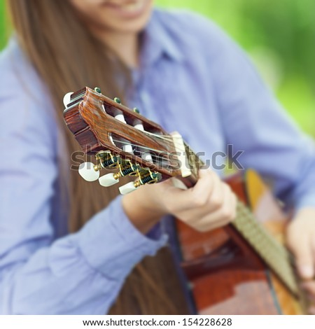 Smiling teenage girl playing guitar, against green of summer park.