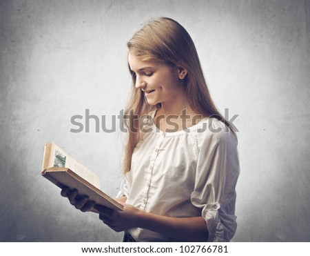 Smiling teenage girl reading a book