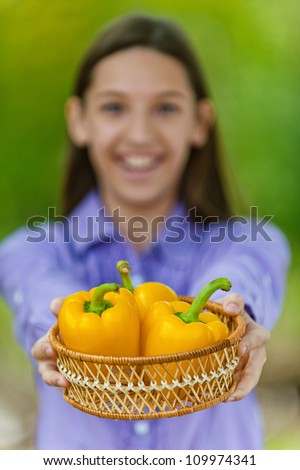 Smiling teenage girl shows basket with orange peppers, against green of summer park.