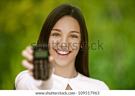 Smiling teenage girl shows cell phone, against green of summer park.