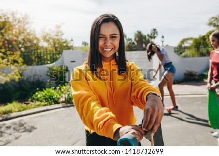 Smiling teenage girl standing in the street holding her longboard with her friends skating in the background. Three young girls practicing skating on street on a sunny day. #1418732699