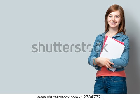 smiling teenage girl standing with books against the wall