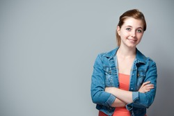 smiling teenage girl standing with crossed arms