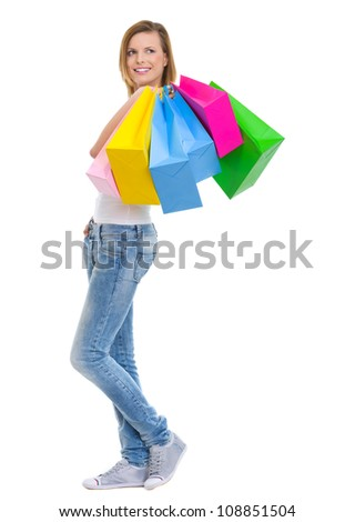 Smiling teenage girl with shopping bags looking on copy space - stock photo
