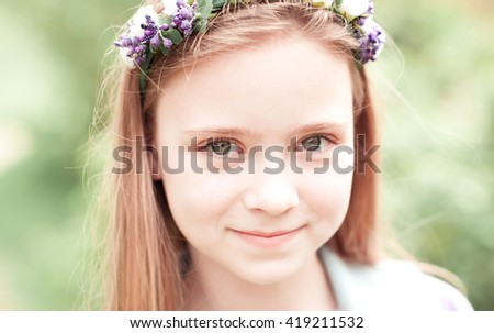 Smiling teenage girl 10-12 year old posing outdoors. Looking at camera.  Wearing