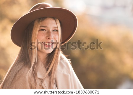 Smiling teenage girl 13-14 year old wearing hat and coat over autumn nature background closeup. Looking at camera. Teenagerhood. Happiness.   Stock photo ©