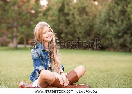Smiling teenage girl 14 -16 year old wearing stylish clothes in park. Looking at camera. Posing outdoors.  Stock photo ©