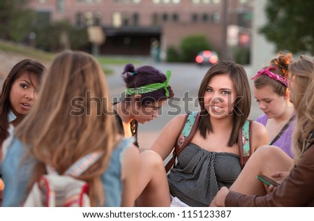 Smiling teenage student with group of friends on campus - stock photo