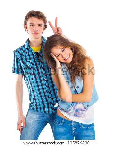 Smiling teenager boy indulge his pretty girlfriend. Isolated on white background.