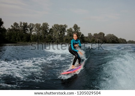 Smiling teenager boy riding on the orange wakeboard having healthy summertime on the river on the background of sky and trees #1205029504