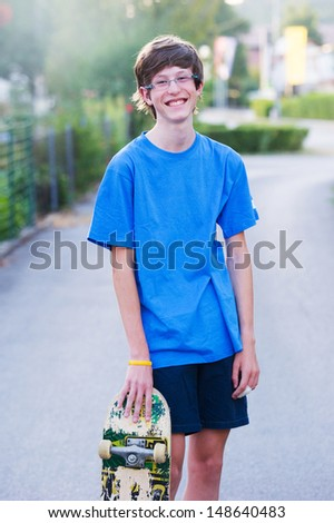 Smiling teenager holding his skateboard