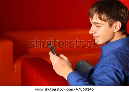 smiling teenager in the room with mobile phone