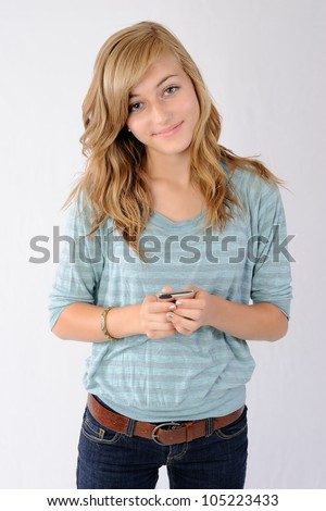 Smiling Teenager with Smartphone. Happy thirteen year old girl smiling at the viewer while holding a smartphone device. Note: Not Isolated.