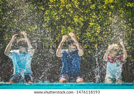 Smiling teenagers splash water with their hands. Young male enjoying days off of school relaxing in the swimming pool. Happy people enjoy summer holiday together Youth carefree relax happiness concept #1476118193