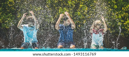 Smiling teenagers splash water with their hands. Young male enjoying days off of school relaxing in the swimming pool. Happy people enjoy summer holiday together Youth carefree relax happiness concept #1493116769