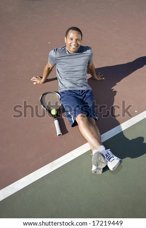 Smiling tennis player sitting down on the tennis court with his racket and ball. Vertically framed photo.
