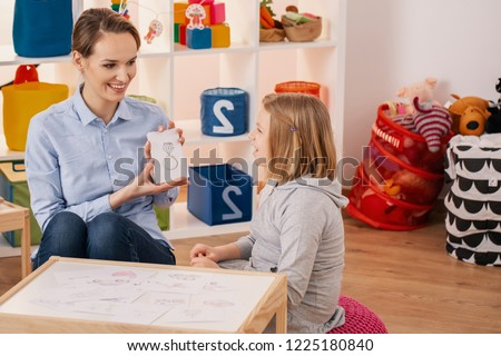 Smiling therapist showing picture of ring during meeting with autistic girl