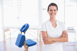 Smiling therapist standing with arms crossed in medical office