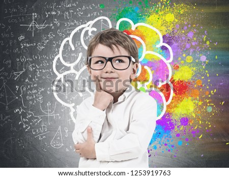 Smiling thinking little boy wearing white shirt and glasses standing near blackboard with colorful brain sketch drawn on it. Concept of creative thinking