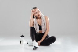 Smiling tired young woman athlete with towel and bottle of water over gray background
