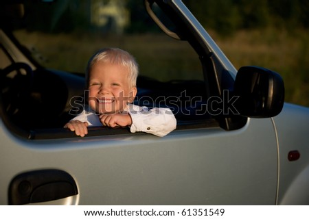 Smiling toddler boy sitting in the car.