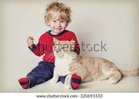 Smiling toddler boy with his pet cat. Vintage toned image. Focus on cat\'s face.