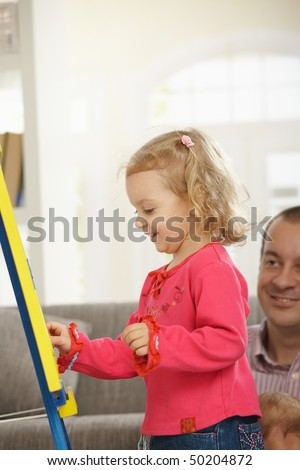 Smiling toddler drawing on board, dad watching in background of living room.
